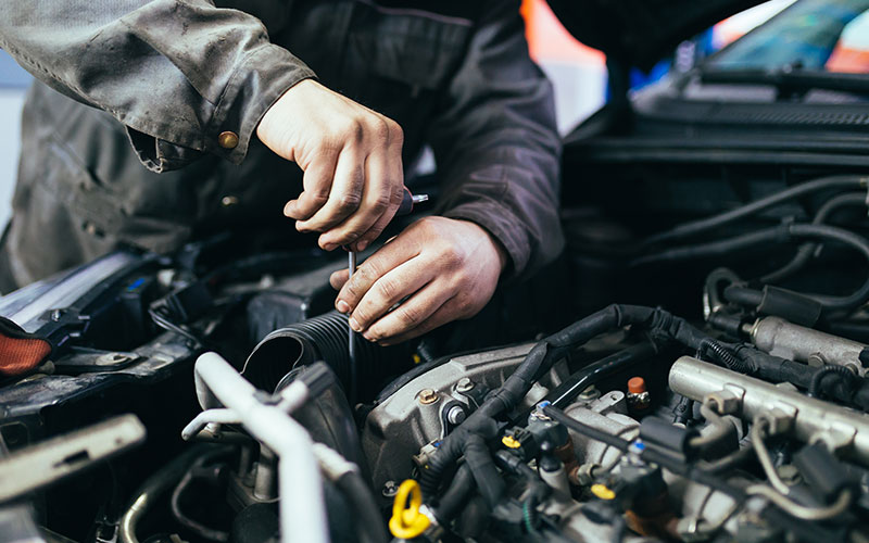 Close up of mechanic working in engine bay of a vehicle