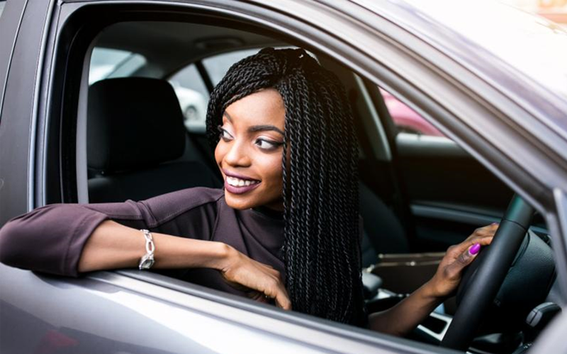 Happy lady in driver's seat of her car