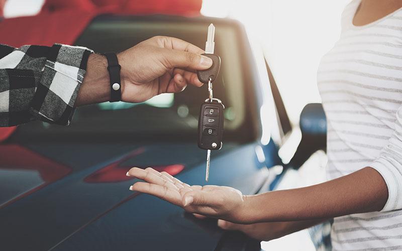 Salesman handing over car keys to customer