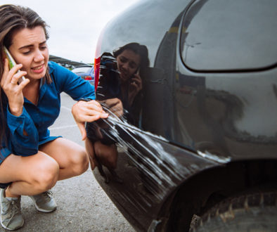 Distressed lady kneeling beside scratched black car on phone call