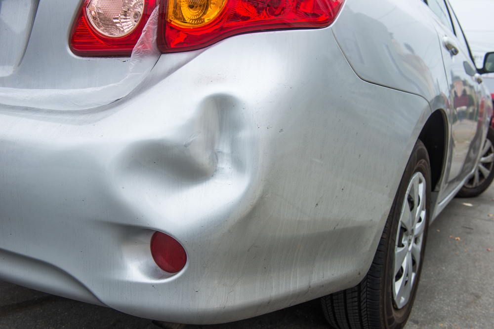 Sliver sedan car with a dent in the right rear bumper