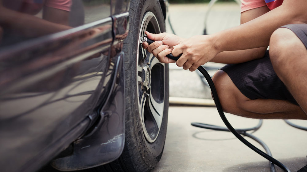 Person using an air pump to inflate vehicle's tyre